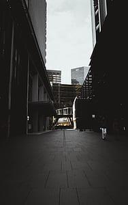 gray concrete sidewalk between buildings