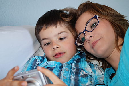 boy holding gray compact camera beside woman wearing black framed eyeglasses