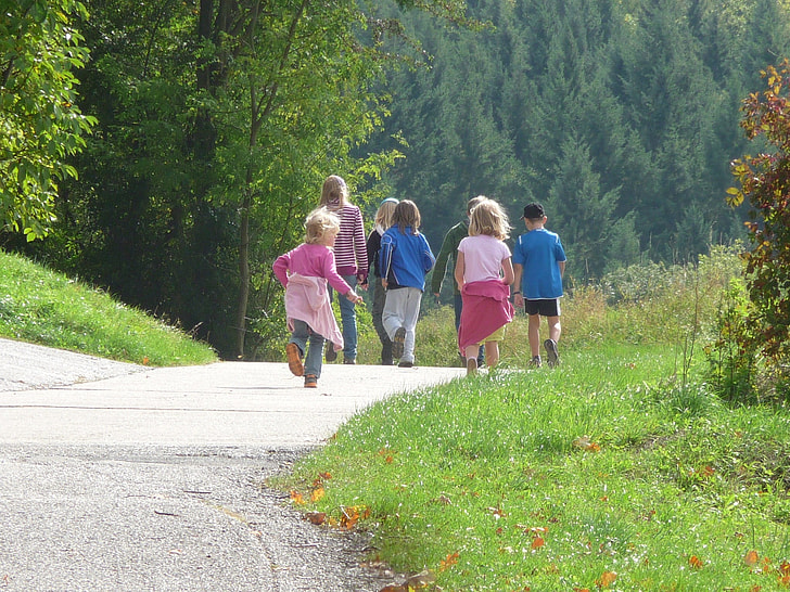 photography of group children running on road