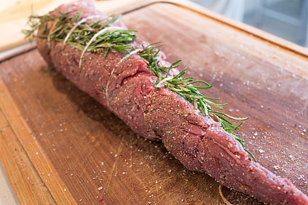 preparing meat with rosemary, salt and pepper
