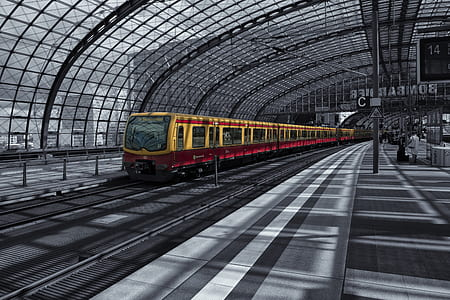 selective color photography of yellow train inside train station