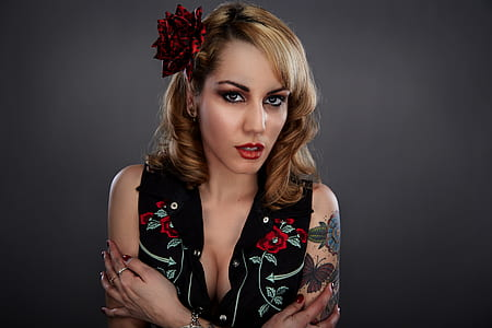 Woman in Black Red and Green Floral Sleeveless Shirt With Red Flower on Her Head and Butterfly Tattoo on Her Left Arm