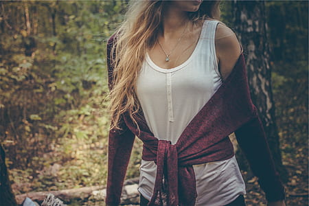 woman wearing white tank top and red sweater on forest