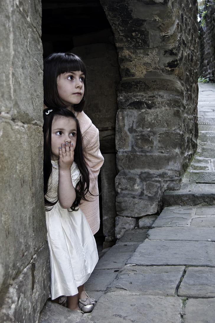 girl in white dress covering her mouth beside girl in beige dress