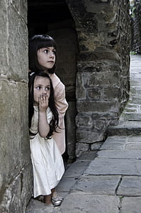 girl in white dress covering her mouth beside girl in beige dress