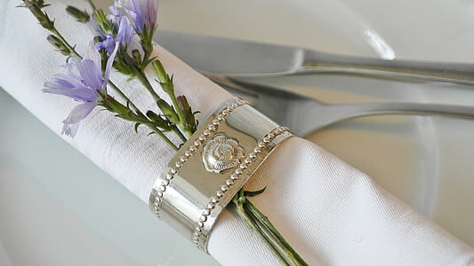 purple petaled flower clipped by silver-colored napkin ring