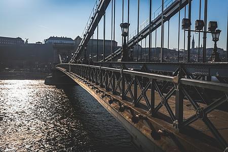 Brass Bridge Near High Rise Building Under Blue Sky