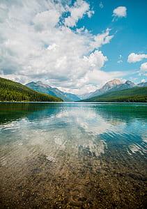 photo of calmed body of water near mountain