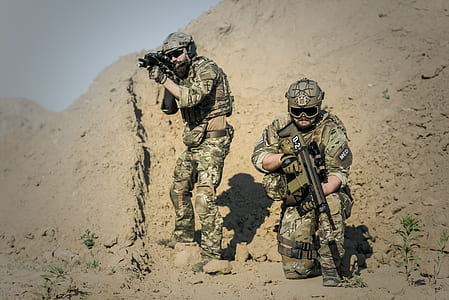 two soldiers with weapons at the field during day