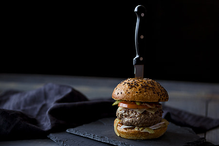 burger with slice of tomato and lettuce with kitchen knife