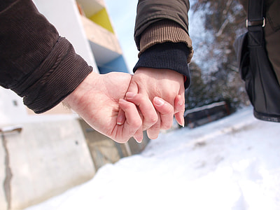 two person holding hands during daytime
