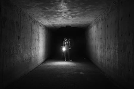 grayscale photo of man holding lamp inside a tunnel