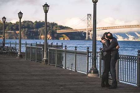 man and woman kissing beside fence