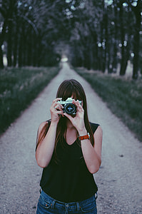 woman in black sleeveless top holding grey bridge camera at daytime