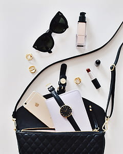 black sunglasses beside lipstick and bag