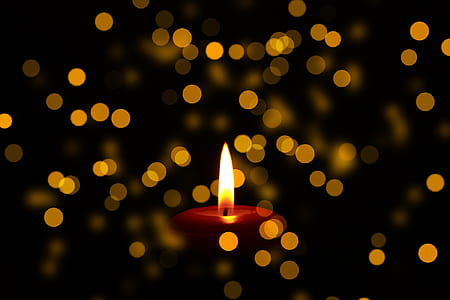 close up photo of lighted red candle bokeh photography