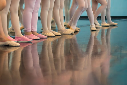 ballerinas wearing leggings and shoes reflecting on wood floor