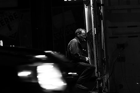 grayscale photo of man sitting while smoking