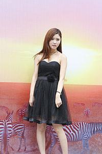 woman wearing black sweetheart neckline mini dress standing near wall with zebra digital wallpaper