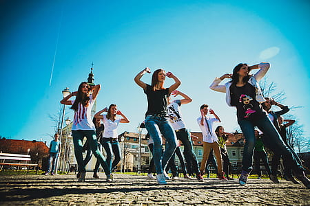 group of people dancing on open field during daytime