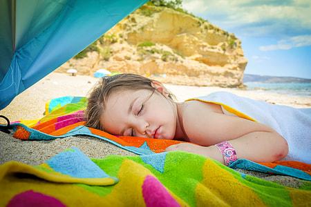 girl sleeping on orange, blue, and green textile near beach