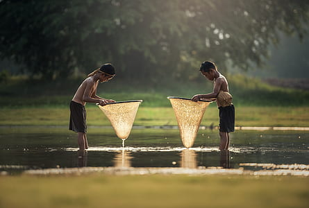 two boys in body of water holding fish nets