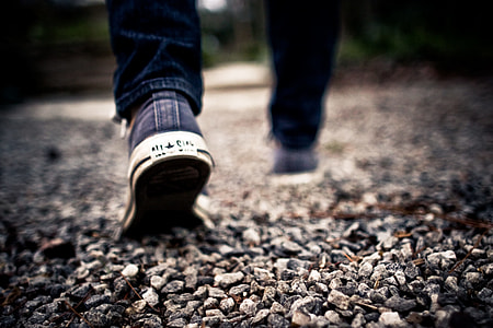 photo of person walking wearing Converse shoes