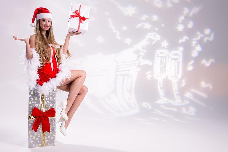 woman wearing Santa costume holding white gift box