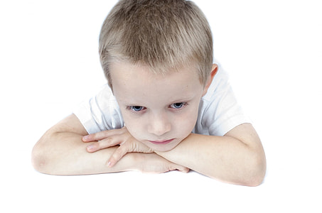 boy wearing white shirt arms and head on table