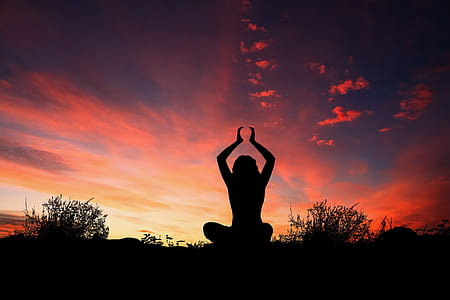 silhouette photography of woman doing yoga during golden hour