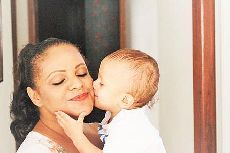 baby kissing woman's cheeks