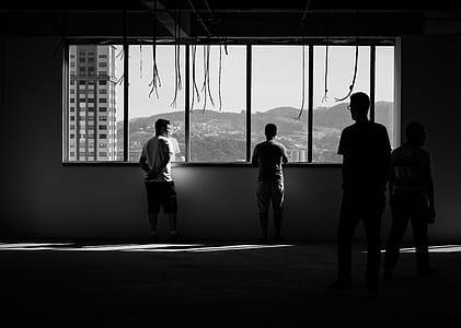silhouette photo of people standing near window