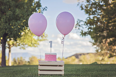 pink cake and balloons on wooden table during daytime