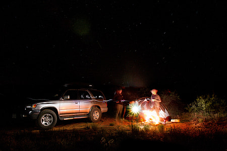 two person standing near car and black tent during night time