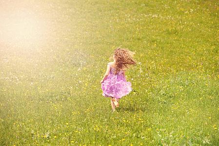 girl in purple sleeveless dress walking on green grass field