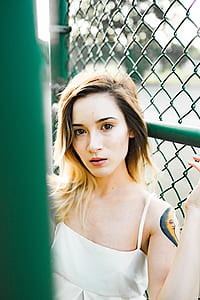 woman wears white sleeveless top leaning on green fence