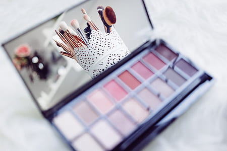 makeup palette with makeup brush set reflected on mirror