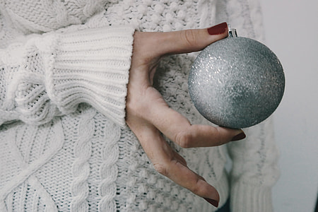 Person holding a silver Christmas decoration ball