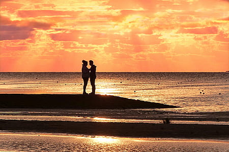 silhouette of man and woman on shore under orange sunset