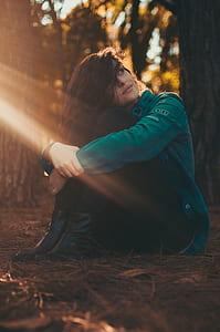 Selective Focus Photography of Woman in Green Jacket and Black Pants Sitting on Field Surrounded With Trees
