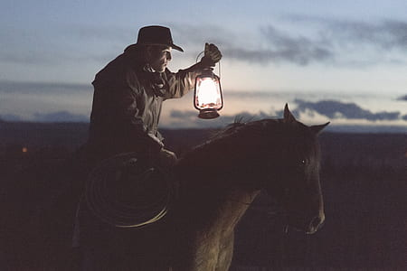 cowboy holding lantern riding on horse