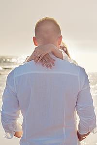 man wearing white dress shirt near ocean