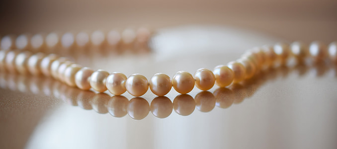closeup photo of beaded brown pearl necklace