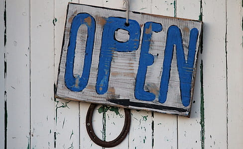 brown and blue wooden Open hanging signboard on white painted wall