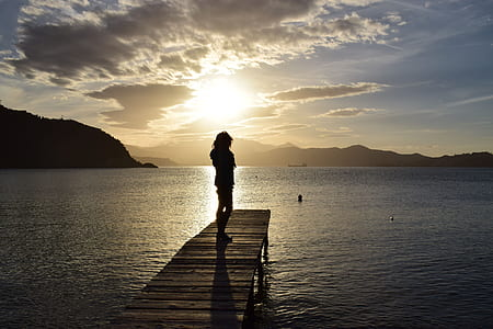 silhouette of person on brown wooden dock during twilight