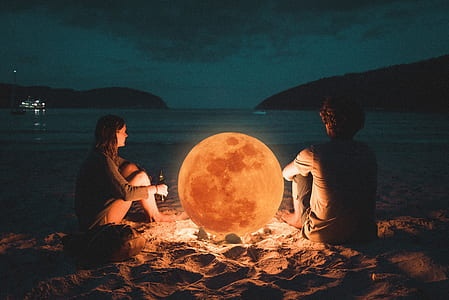 man and woman sitting on sand near sea shore during night time