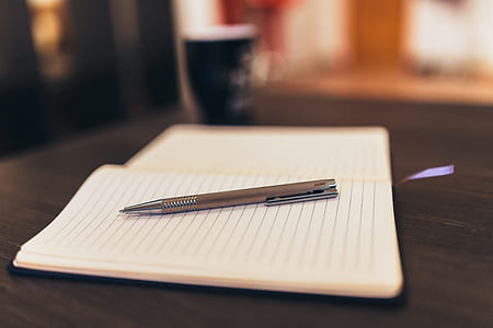 selective focus photography of click pen on white lined paper