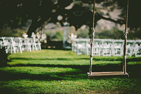 brown wooden base swing near white wooden chairs at daytime