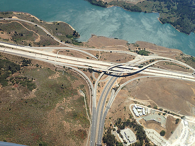 aerial photography of road near body of water during daytimer