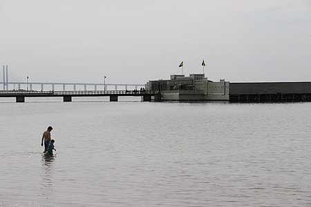 man walking at the sea near a bridge